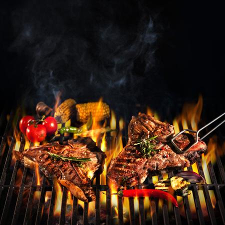 쇠고기 T-bone 스테이크가 불에 그릴에 붙어 있습니다. 스톡 콘텐츠 - 76548392