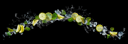 Lime and lemon pieces with mint and ice in water splash Stock Photo