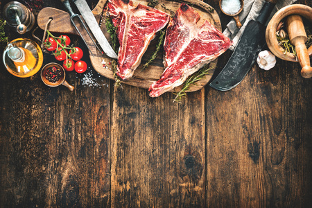 Raw dry aged t-bone steaks for grill with fresh herbs, vegetables and cleaver on rustic wooden board