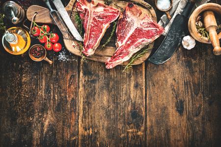 Bistecche di bistecca con l'osso invecchiate crude per la griglia con le erbe, le verdure e la mannaia fresche sul bordo di legno rustico Archivio Fotografico - 76548398