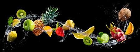 Frutta su sfondo nero con spruzzi d'acqua Archivio Fotografico - 76548399