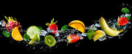 水のしぶきと黒の背景の果物