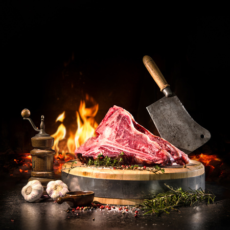 Raw dry aged t-bone steaks for grill with fresh herbs and cleaver 版權商用圖片 - 76548402