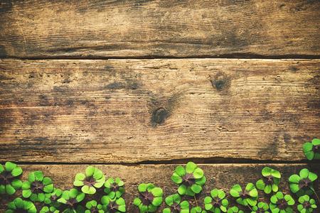 Hojas del trébol en el fondo de madera viejo. Trébol afortunado. Fondo del día de St.Patrick con el copyspace para el texto Foto de archivo - 76548403