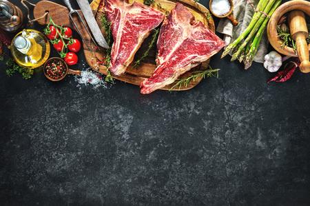rusty background: Raw dry aged t-bone steaks for grill with fresh herbs and vegetables Stock Photo