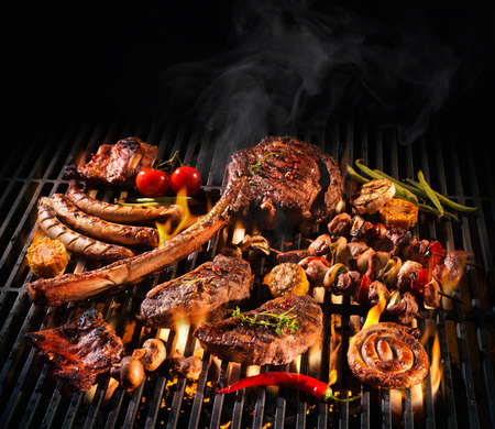 Assorted delicious grilled meat with vegetables over the coals on a barbecue