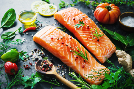 europe: Fresh salmon fillet with aromatic herbs, spices and vegetables. Balanced diet or cooking concept