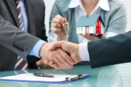 customer: Estate agent shaking hands with customer after contract signature
