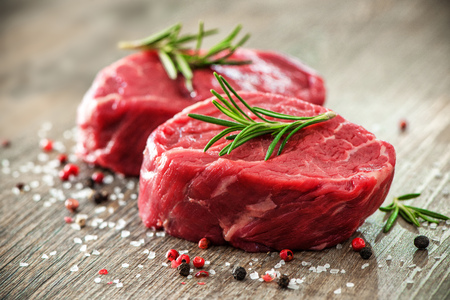 cutting: Raw beef fillet steaks with spices on wooden background