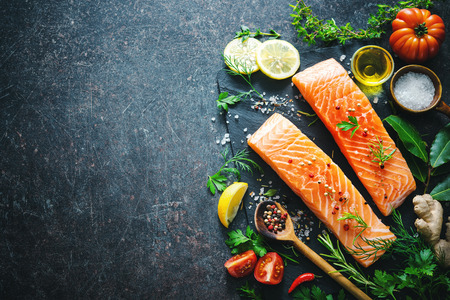 dark: Fresh salmon fillet with aromatic herbs, spices and vegetables. Balanced diet or cooking concept