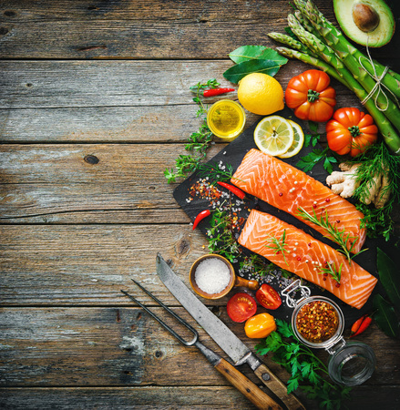 cutting: Fresh salmon fillet with aromatic herbs, spices and vegetables. Balanced diet or cooking concept