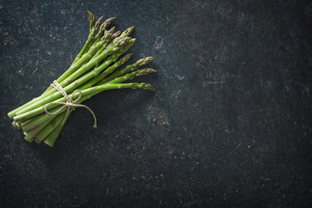 Fresh green asparagus on dark background