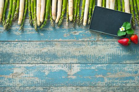 Fresh green and white asparagus with strawberries on wooden background Stock Photo