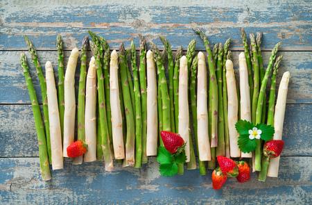 Verse groene en witte asperges met aardbeien op houten achtergrond Stockfoto