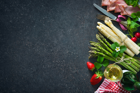 Fresh green and white asparagus with strawberries and wineglas on dark background Stock Photo