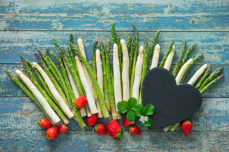 Fresh green and white asparagus with strawberries on wooden background Reklamní fotografie
