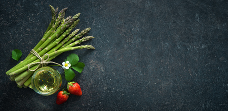 Fresh green asparagus with strawberries and wineglas on dark background