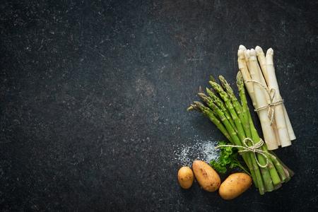 Fresh green and white asparagus on dark background