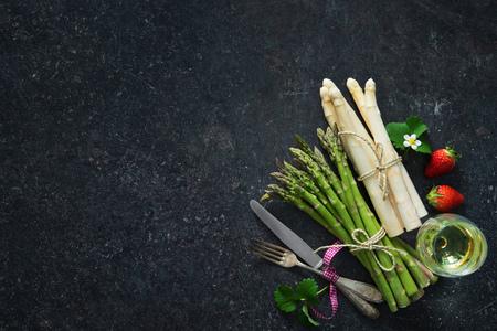신선한 녹색과 흰색 아스파라거스 딸기와 와인 글라스 어두운 배경에
