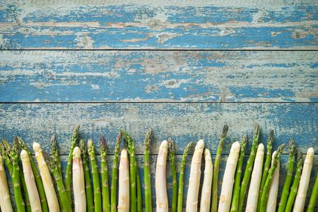木製の背景にイチゴと新鮮な緑と白のアスパラガス