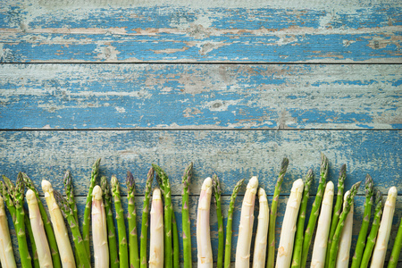 Fresh green and white asparagus with strawberries on wooden background Imagens