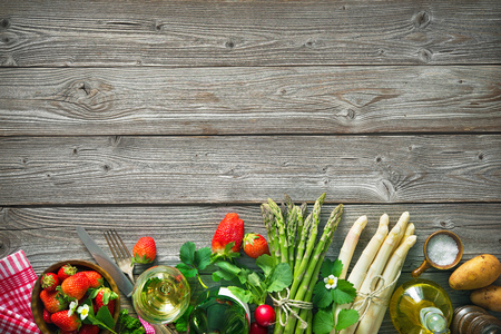 raw: Fresh green and white asparagus with strawberries and wine on wooden background