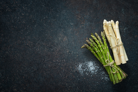 Fresh green and white asparagus on dark background