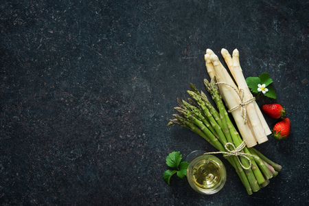 Fresh green and white asparagus with strawberries and wineglas on dark background Stockfoto
