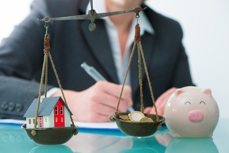 Ahorros o concepto de inversión inmobiliaria con la casa y dinero en efectivo en la escala Foto de archivo - 78093239