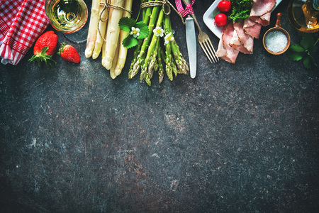 dark: Fresh green and white asparagus with strawberries and wineglas on dark background Stock Photo