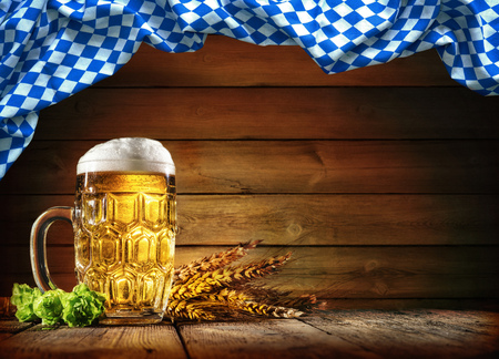 Oktoberfest beer with wheat  and hops on wooden table