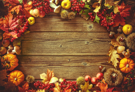 Vintage autumn border from fallen leaves and fruits on the old wooden table. Thanksgiving autumn background