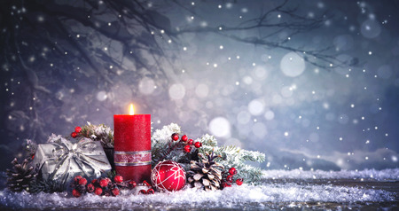 Ozdoba adwentowa z jedną płonącą świecą. Boże Narodzenie w tle