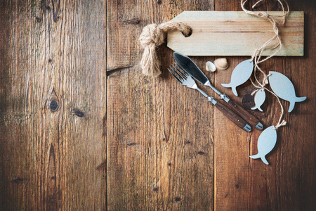 gefesselt: Fischbesteck mit leeren Fisch geformt Tag auf Holztisch mit Kopie Raum gebunden. Menü-Karte für Restaurants Lizenzfreie Bilder