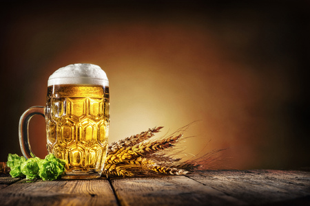 Oktoberfest beer with wheat  and hops on wooden table Stock Photo - 78446618
