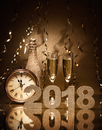 New Years Eve celebration background with pair of flutes, bottle of champagne and a clock Foto de archivo