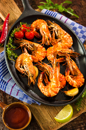 Seafood. Fried grilled shrimp prawns in a pan on wooden table Stock Photo