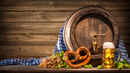 Oktoberfest beer barrel and beer glass with wheat and hops on wooden table Stock Photo