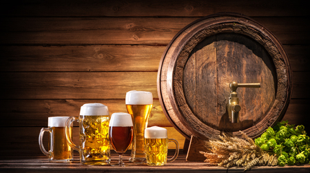 Oktoberfest beer barrel and beer glasses with wheat and hops on wooden table Фото со стока