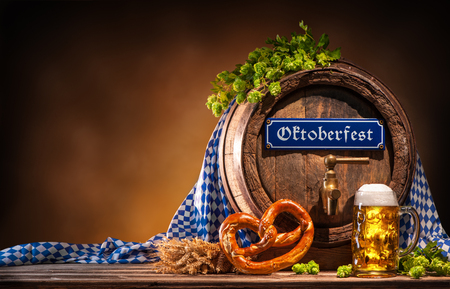comida alemana: Oktoberfest beer barrel and beer glass with wheat and hops on wooden table Foto de archivo