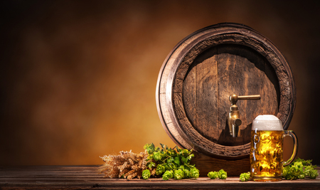 Oktoberfest beer barrel and beer glass with wheat and hops on wooden table Stockfoto