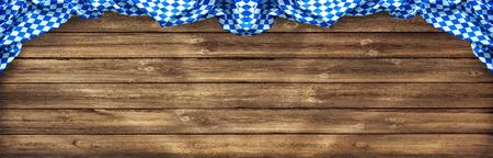 Rustieke achtergrond voor Oktoberfest met Beierse witte en blauwe stof op oude houten bord