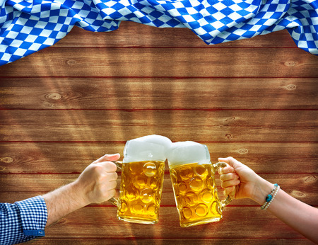 Cheers! Hands holding up beer mugs under Bavarian flag on wooden background