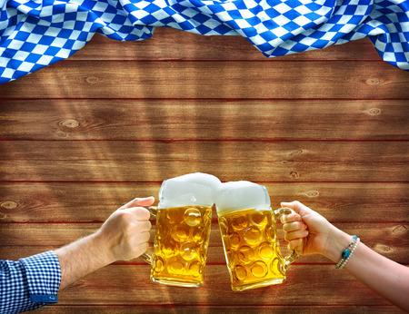 Aclamaciones! Manos sosteniendo tazas de cerveza bajo bandera bávara sobre fondo de madera Foto de archivo - 80125124