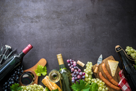 Wine bottles with grapes, cheese, ham and corks on dark background with copy space