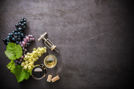 Wineglasses with grapes and corks on dark background with copy space Stock Photo