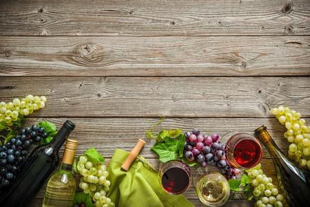 Wine bottles with grapes and corks on wooden background with copy space Stok Fotoğraf - 80125684
