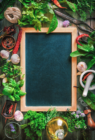 Fresh kitchen herbs and spices on wooden table with a blackboard. Top view Stock Photo