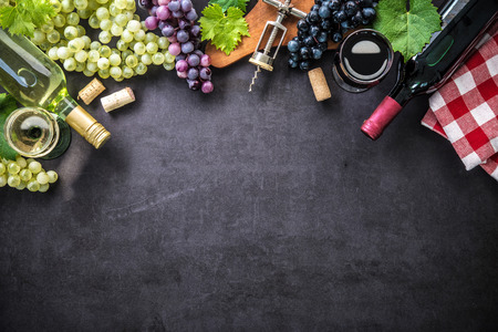 table top: Wine bottles with grapes, cheese, ham and corks on dark background with copy space