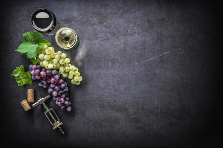 Wijnglazen met druiven en kurken op donkere achtergrond met kopie ruimte Stockfoto
